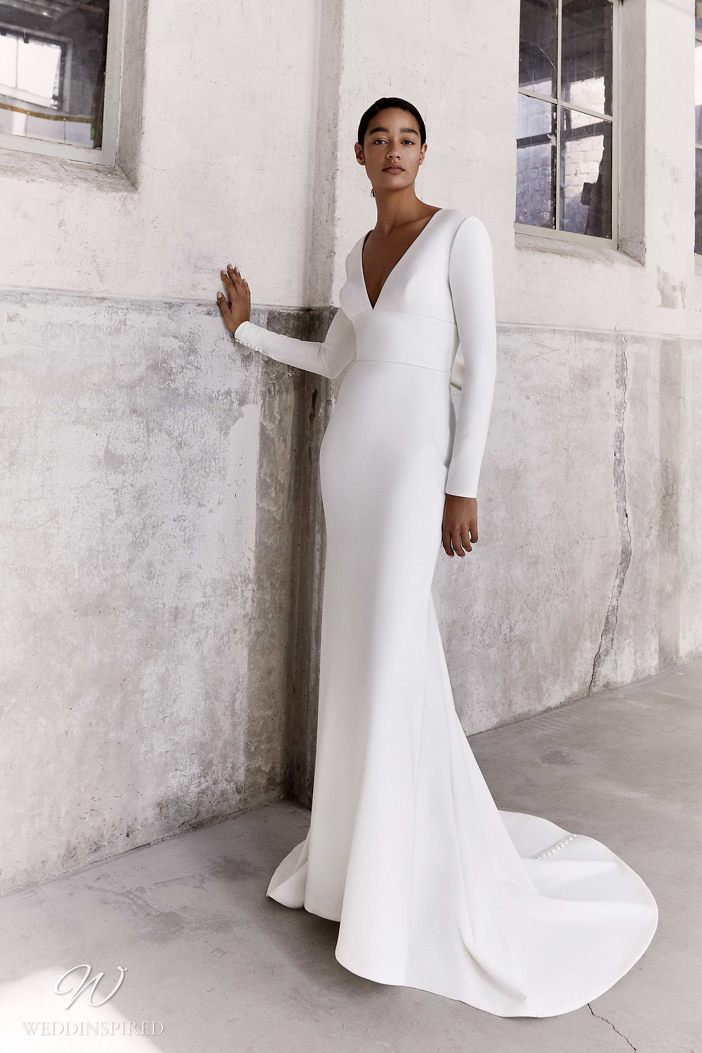A Viktor & Rolf Fall/Winter 2021 simple mermaid wedding dress with long sleeves and a v neck