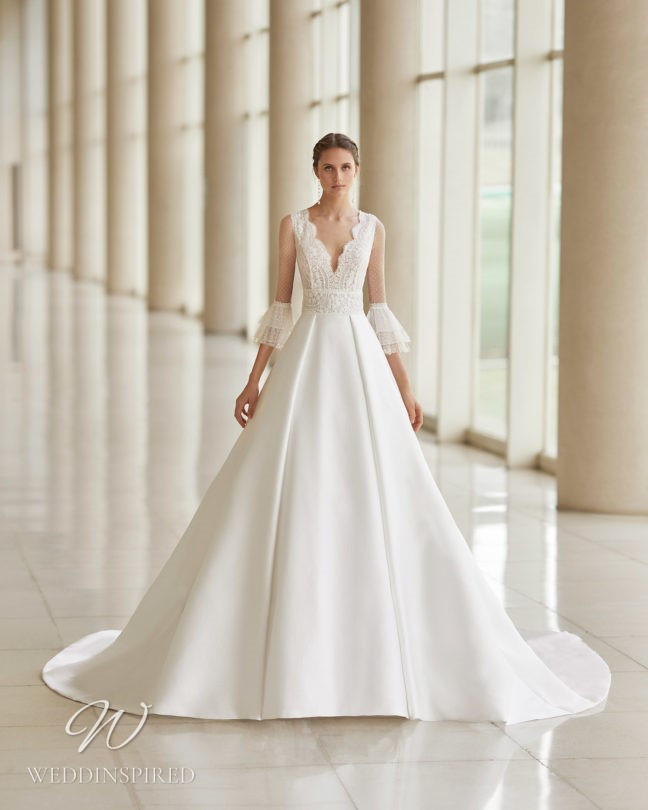 An Aire Barcelona 2021 lace and satin princess ball gown wedding dress with long sleeves and a v neck