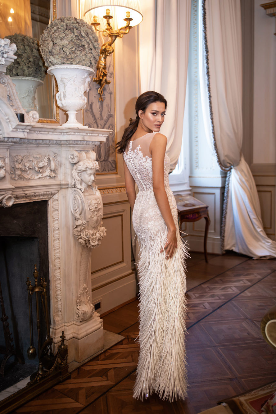 A Milla Nova lace and feathers fitted wedding dress with an illusion top
