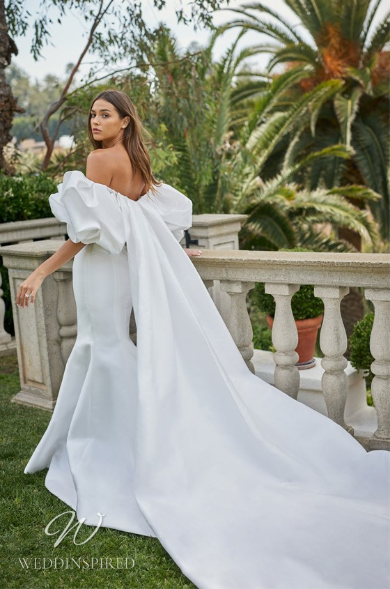 A Monique Lhuillier off the shoulder mermaid wedding dress with puff sleeves and a cape