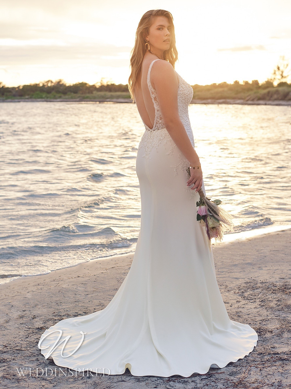 A Rebecca Ingram 2021 plus size lace and satin mermaid wedding dress with a low back