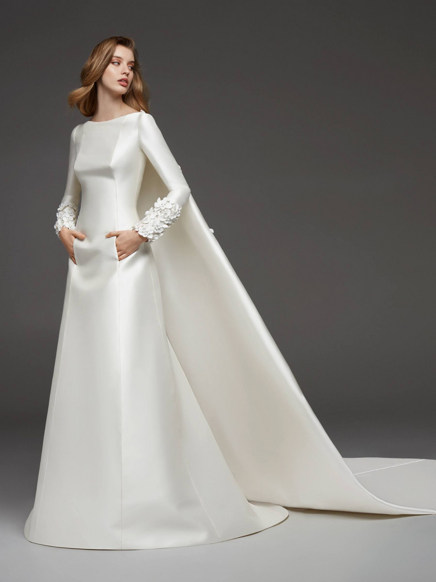 A Pronovias simple modest silk satin A-line wedding dress with long sleeves and pockets