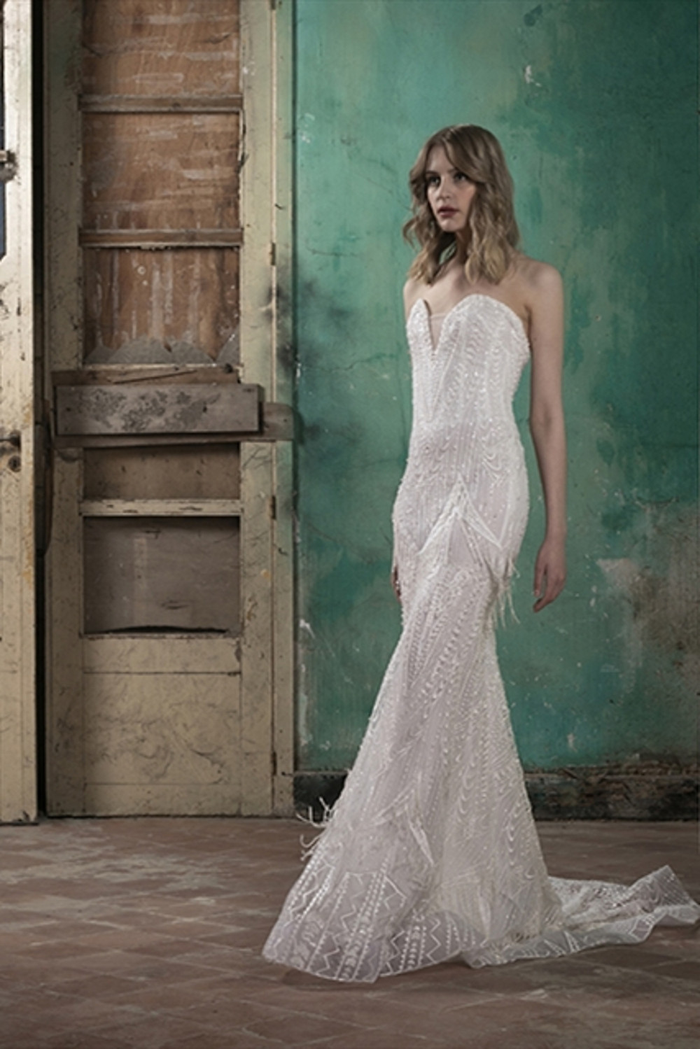 A strapless fitted mermaid  wedding dress featuring a heart-shaped neckline enriched with beaded embroidery and fringe detailing