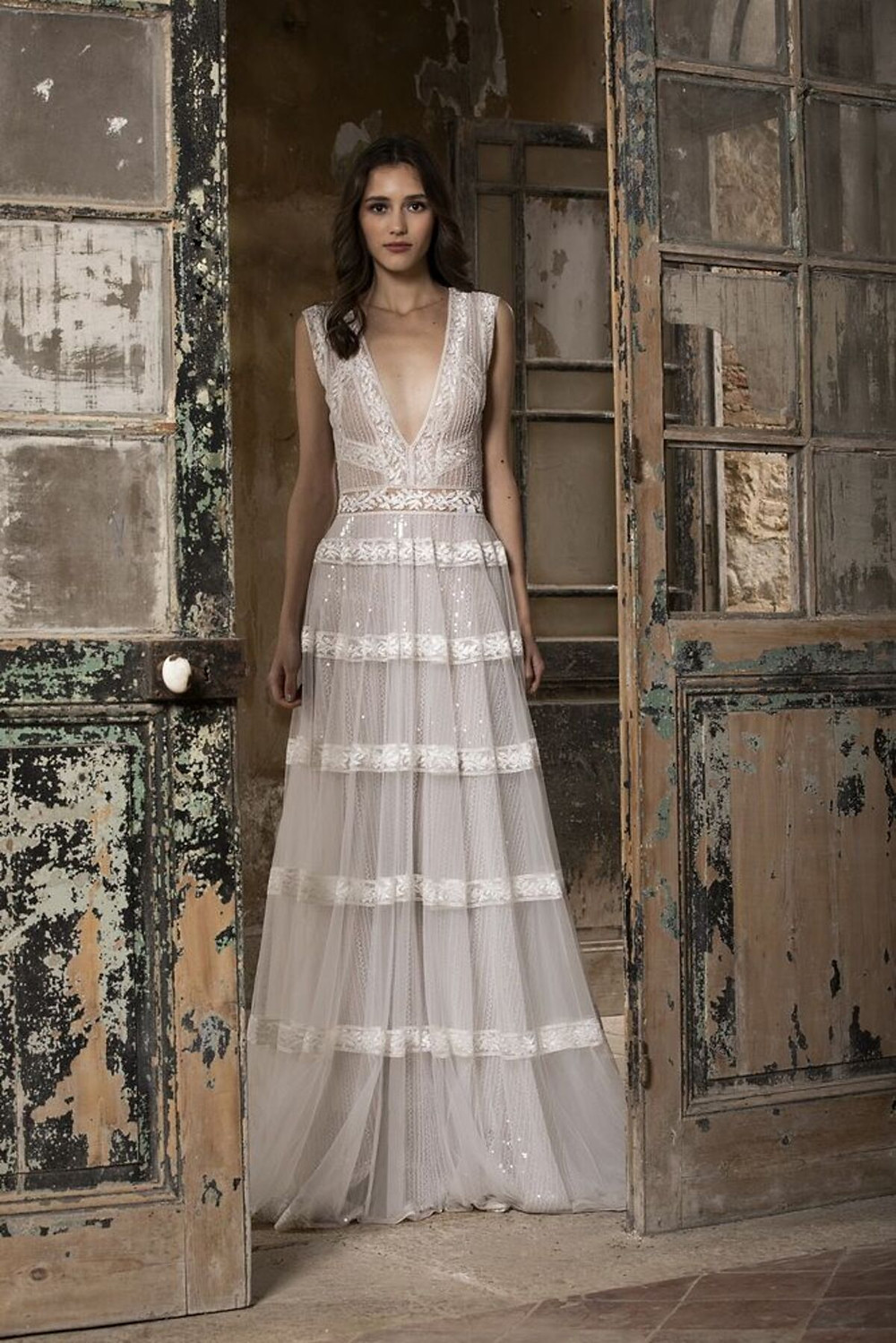 An A-line wedding gown featuring a plunging neckline enriched with delicate lace bands and sequence detailing