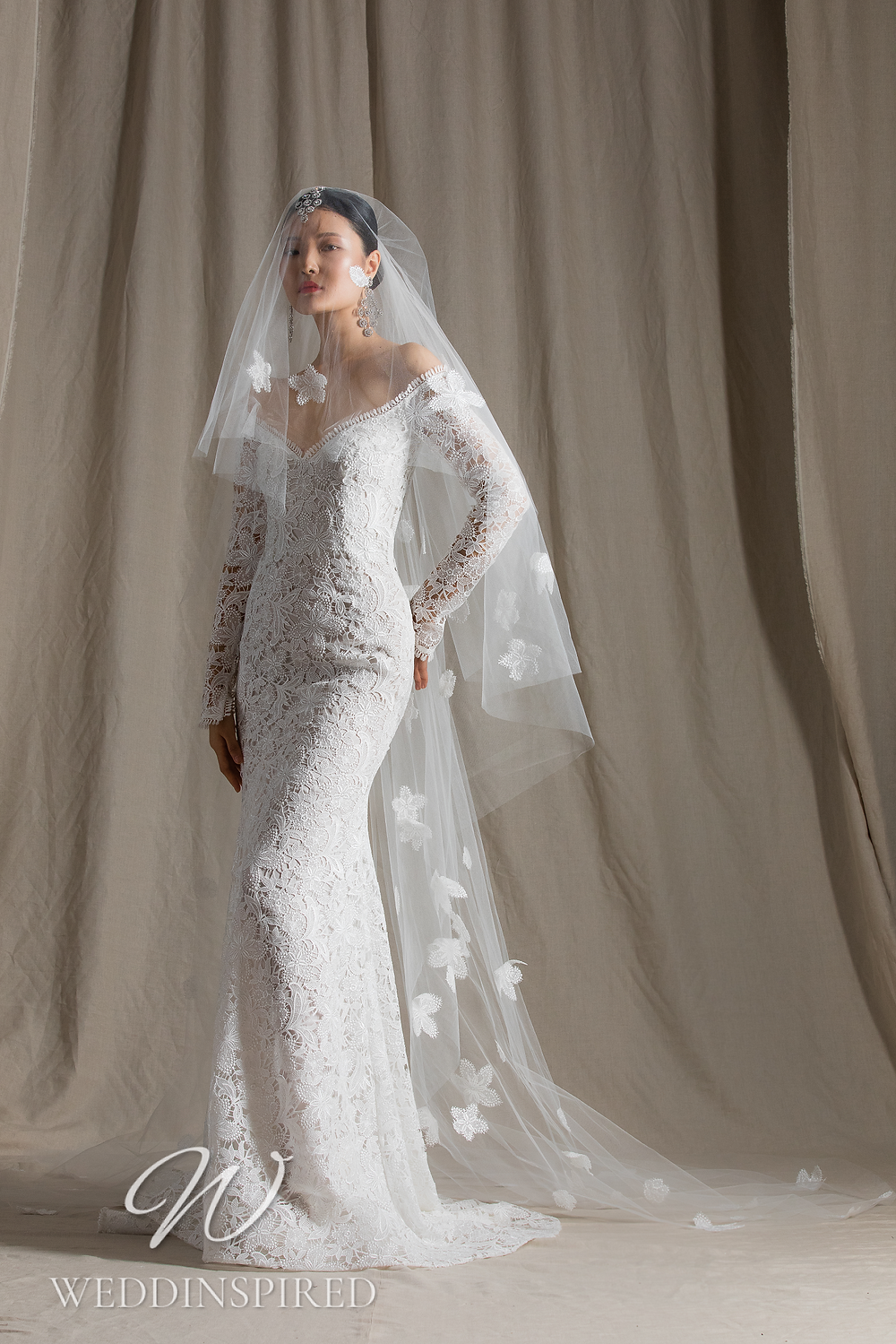 A Naeem Khan 2022 off the shoulder lace mermaid wedding dress with long sleeves