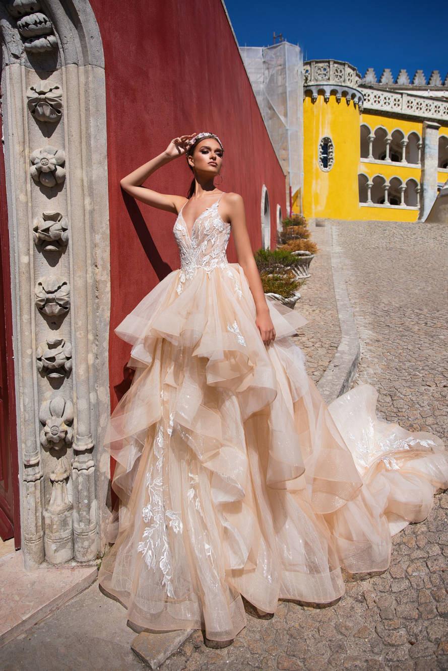 A Milla Nova peach blush tulle ball gown wedding dress with layered ruffle skirt