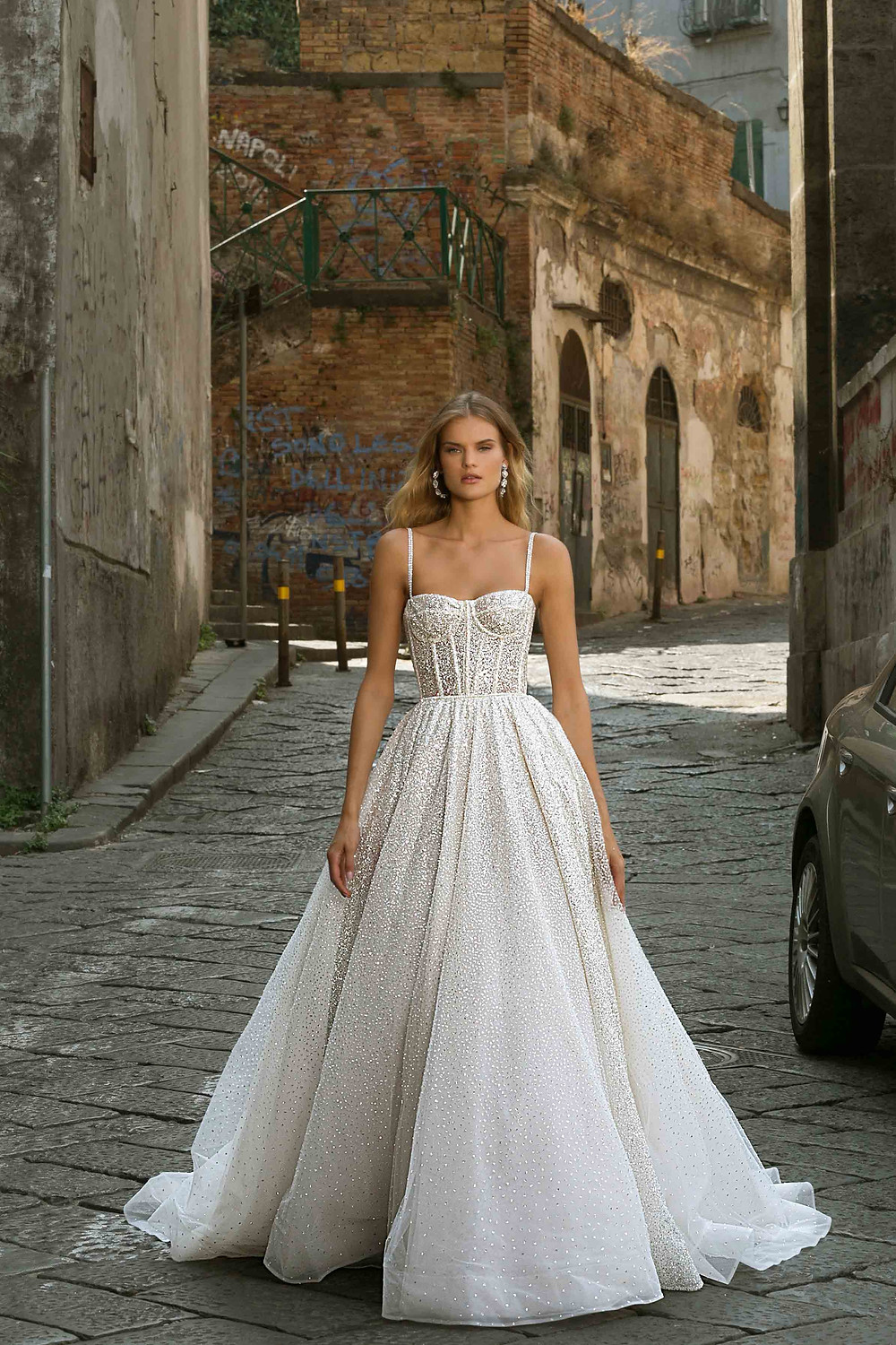 A sparkly ball gown wedding dress, with corset top, thin straps and crystals