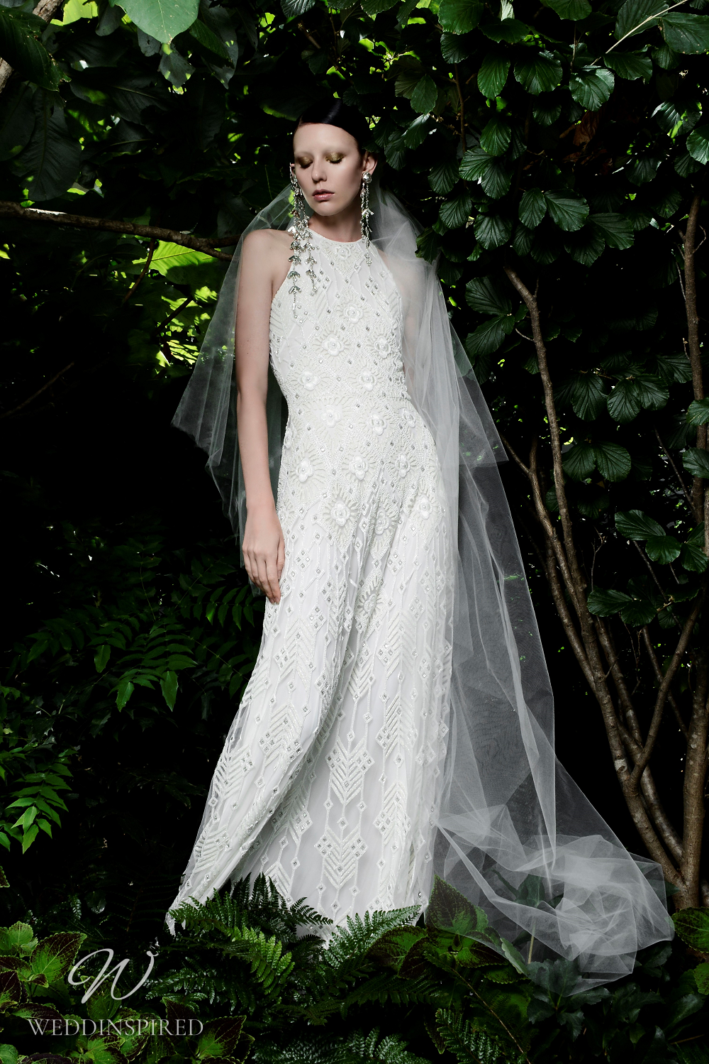 A Naeem Khan Fall 2021 lace A-line wedding dress with a high neckline and a geometric pattern