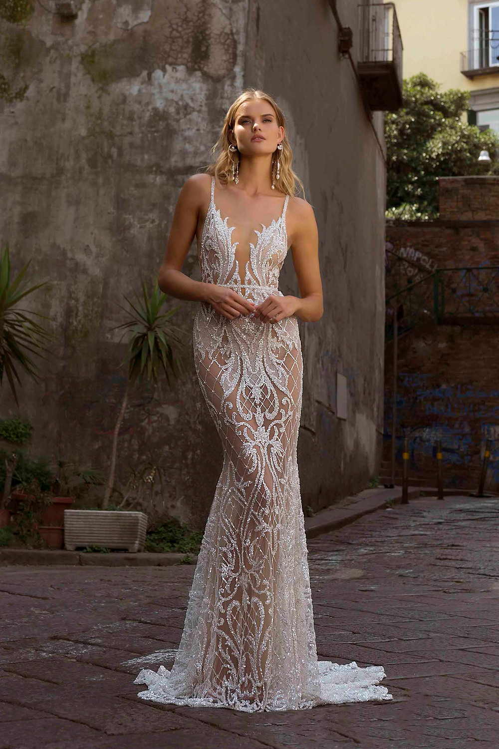 A sparkly, sexy mermaid wedding dress, with thin straps, low v neckline and crystals