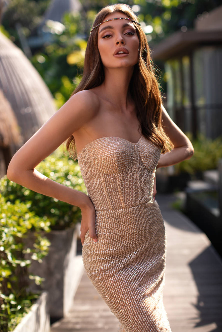 A tight fitting, gold wedding dress with corset top and sweetheart neckline