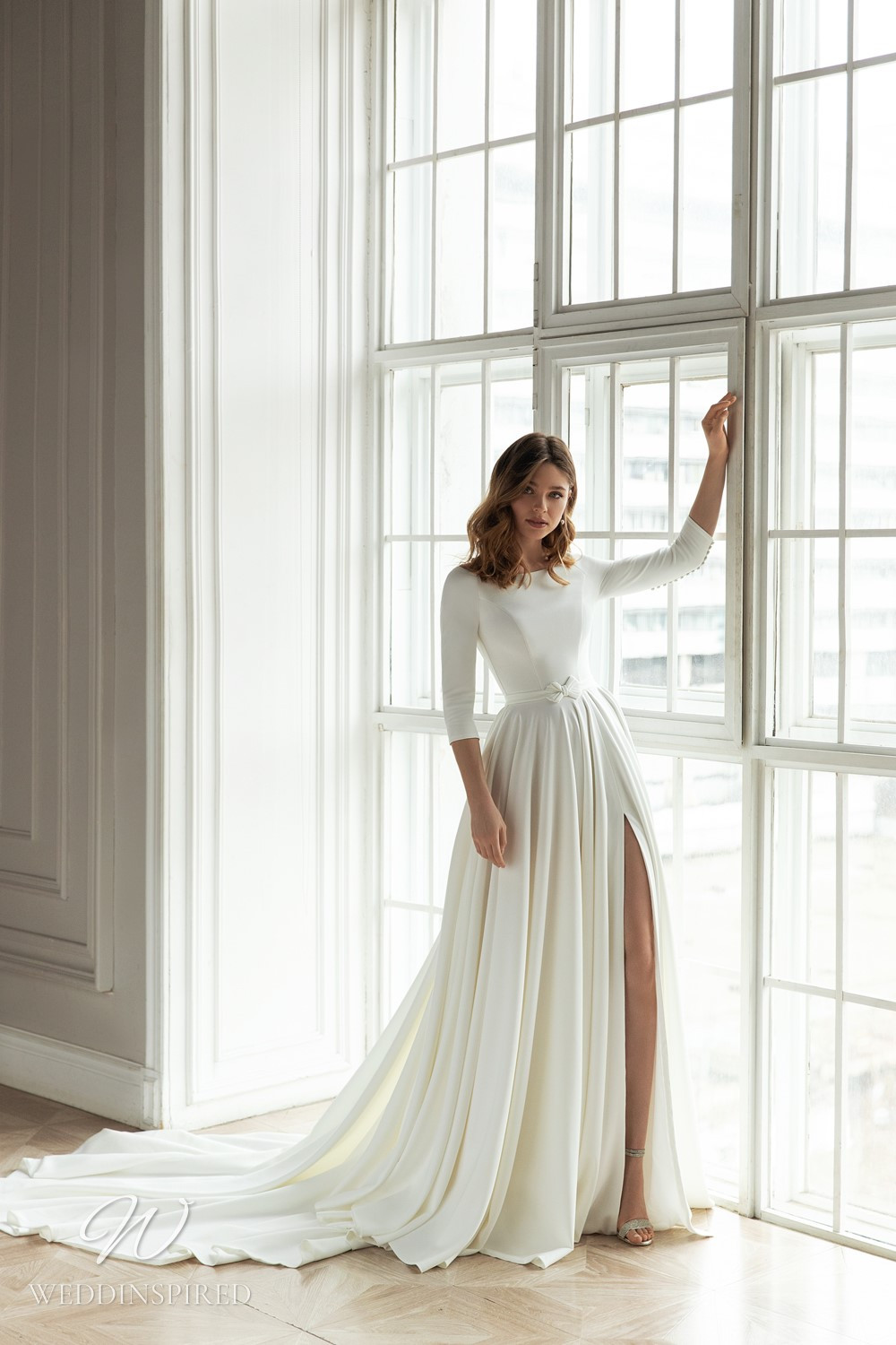 An Eva Lendel 2021 simple crepe A-line wedding dress with long sleeves and a high slit