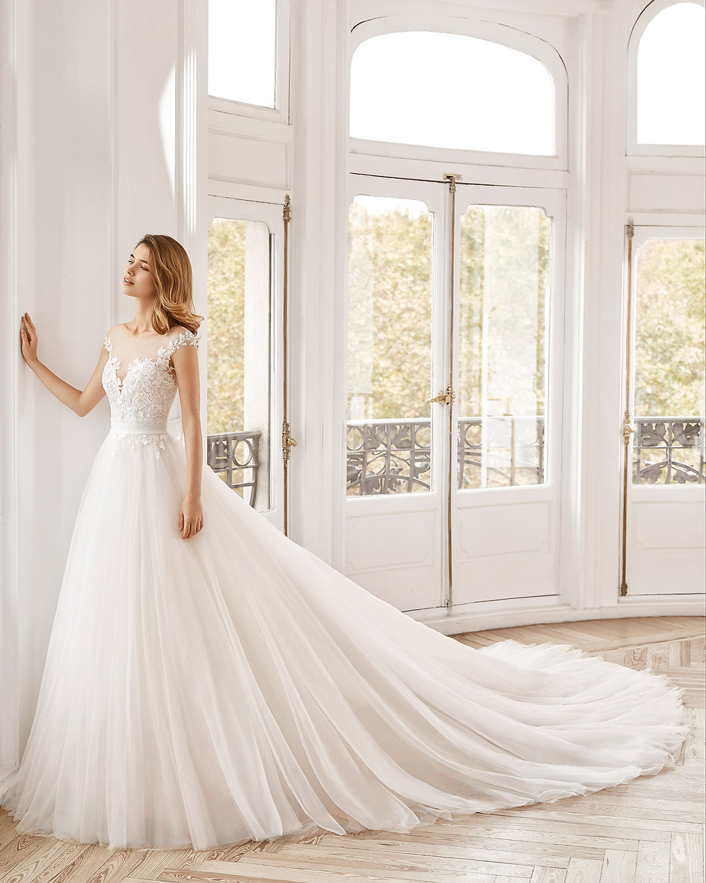 An Aire Barcelona 2020 lace and tulle off the shoulder ball gown wedding dress with a train