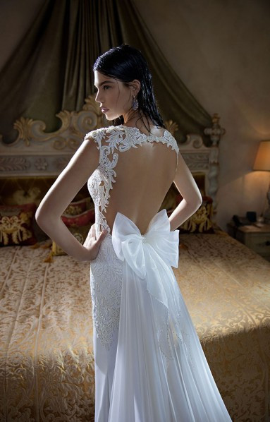 A Berta lace and chiffon fitted wedding dress with a keyhole back and a bow