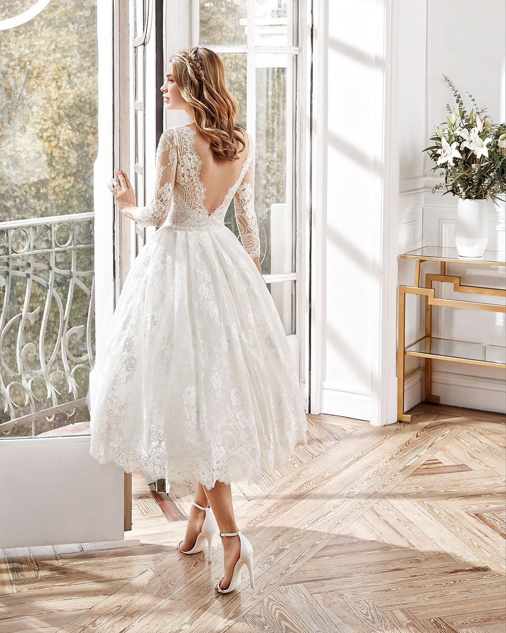 An Aire Barcelona 2020 romantic lace tea length wedding dress with a low back and long sleeves