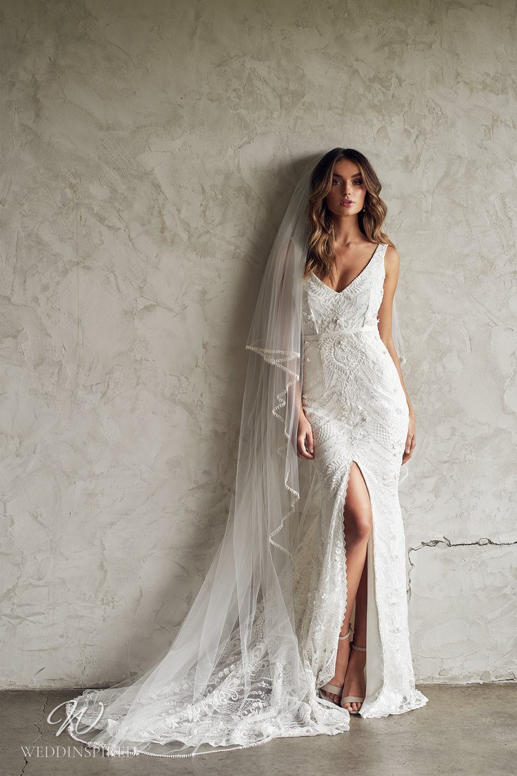 An Anna Campbell 2020 fitted lace wedding dress with a v neck, a slit and a veil