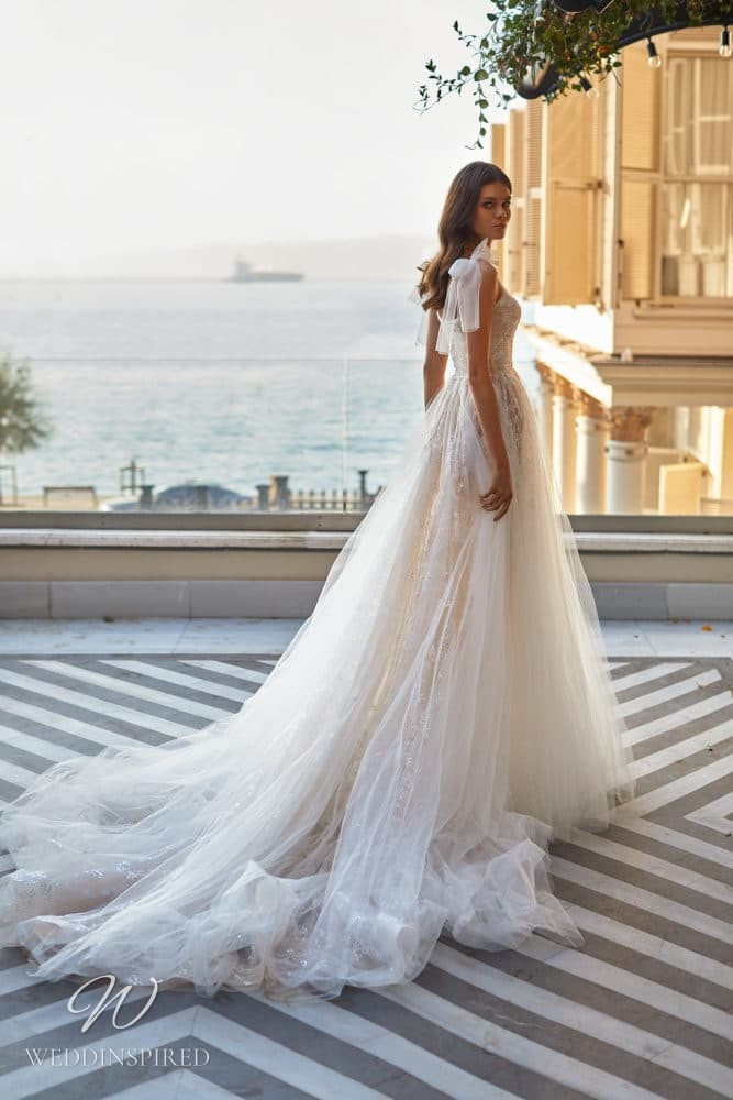A Milla Nova 2021 ivory tulle A-line wedding dress with a train and bow straps