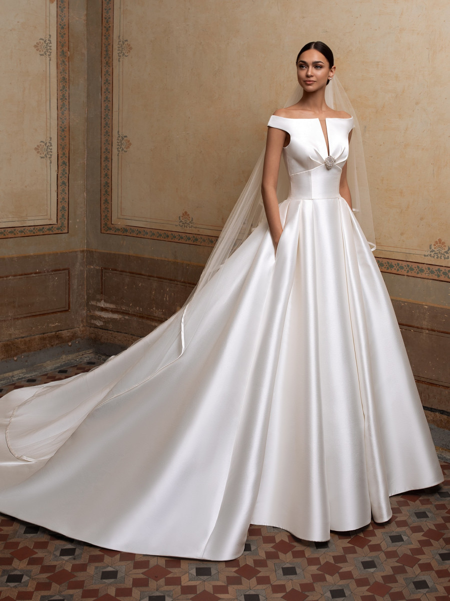A Pronovias simple off the shoulder silk ball gown wedding dress with pockets