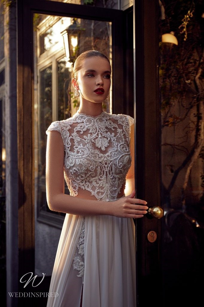 A Julie Vino 2021 ivory lace and chiffon A-line wedding dress with cap sleeves and a high slit