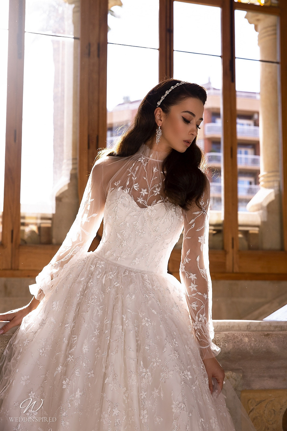 A Maks Mariano princess ball gown wedding dress with long sleeves and an illusion top
