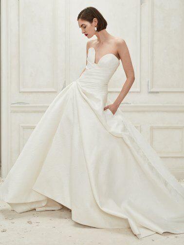 An Oscar de la Renta simple strapless crepe ball gown wedding dress with pockets