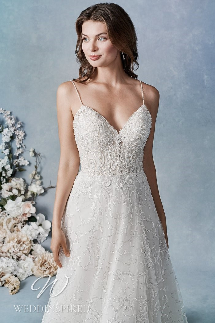 A Kenneth Winston 2021 lace A-line wedding dress with a v neck and straps