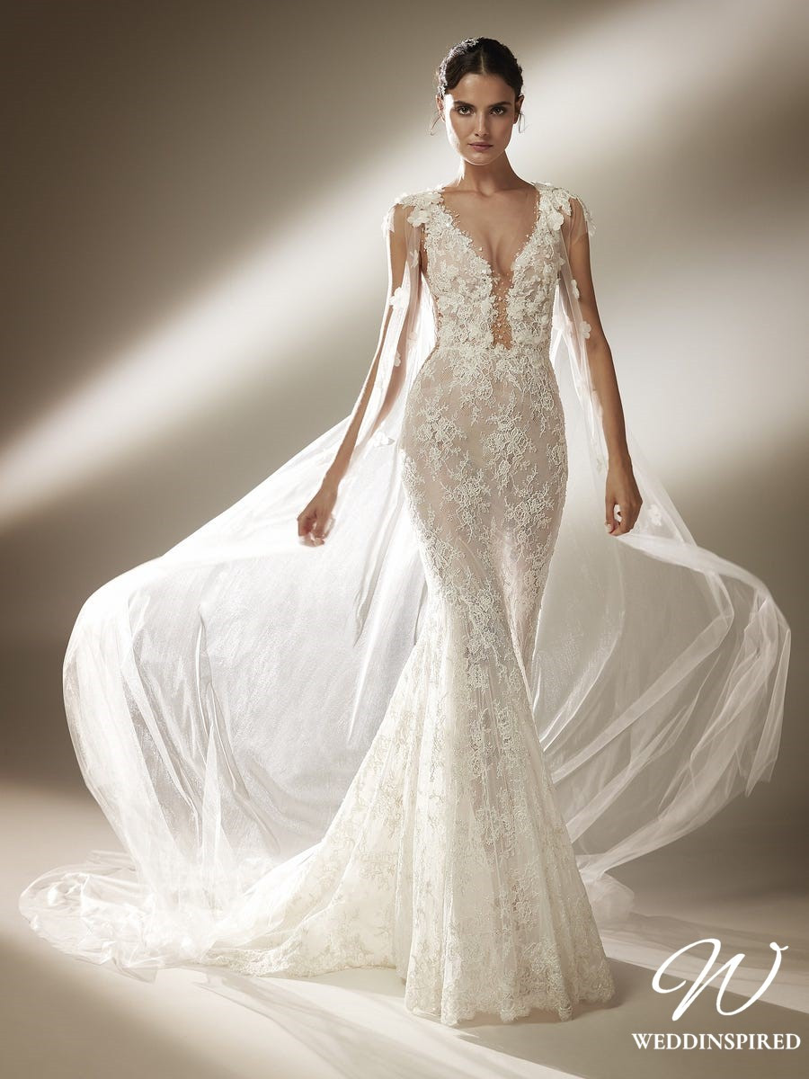 An Atelier Pronovias lace mermaid wedding dress with a low v neckline and a tulle cape