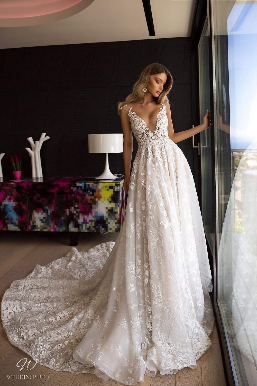 A Tina Valerdi lace A-line wedding dress with a deep v neckline and a train