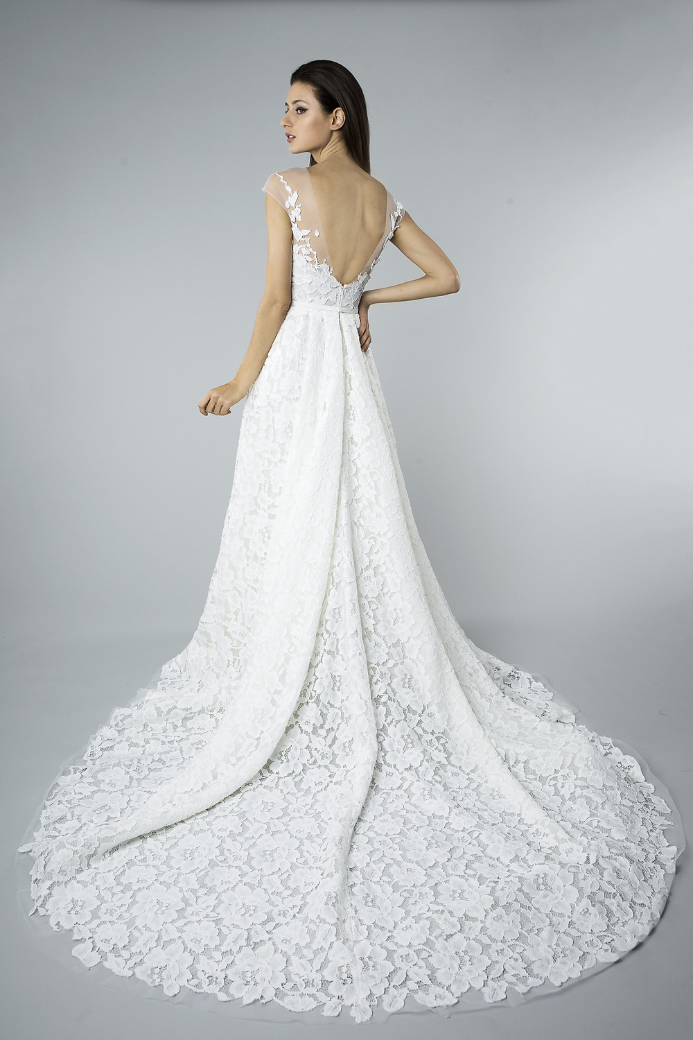 A Mira Zwillinger lace and mesh A-line wedding dress with a low back