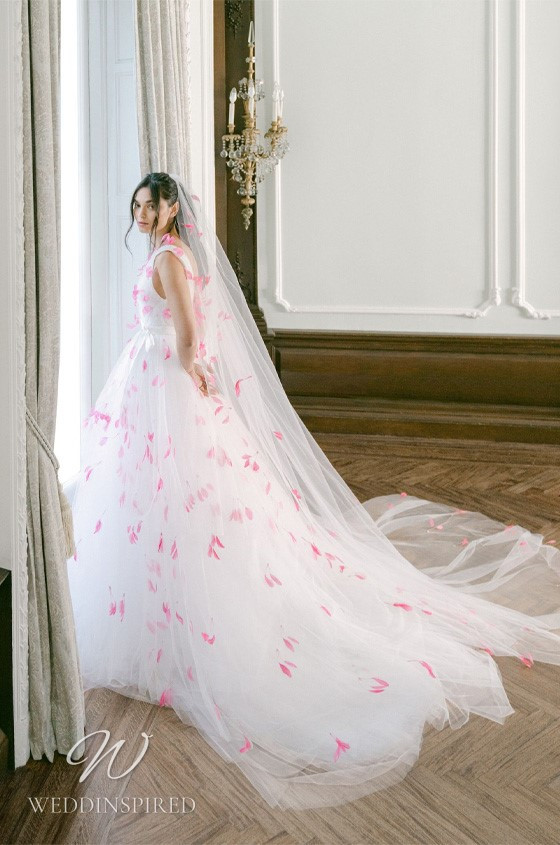 A Monique Lhuillier Fall 2021 tulle A-line wedding dress with pink flowers, straps and a v neck