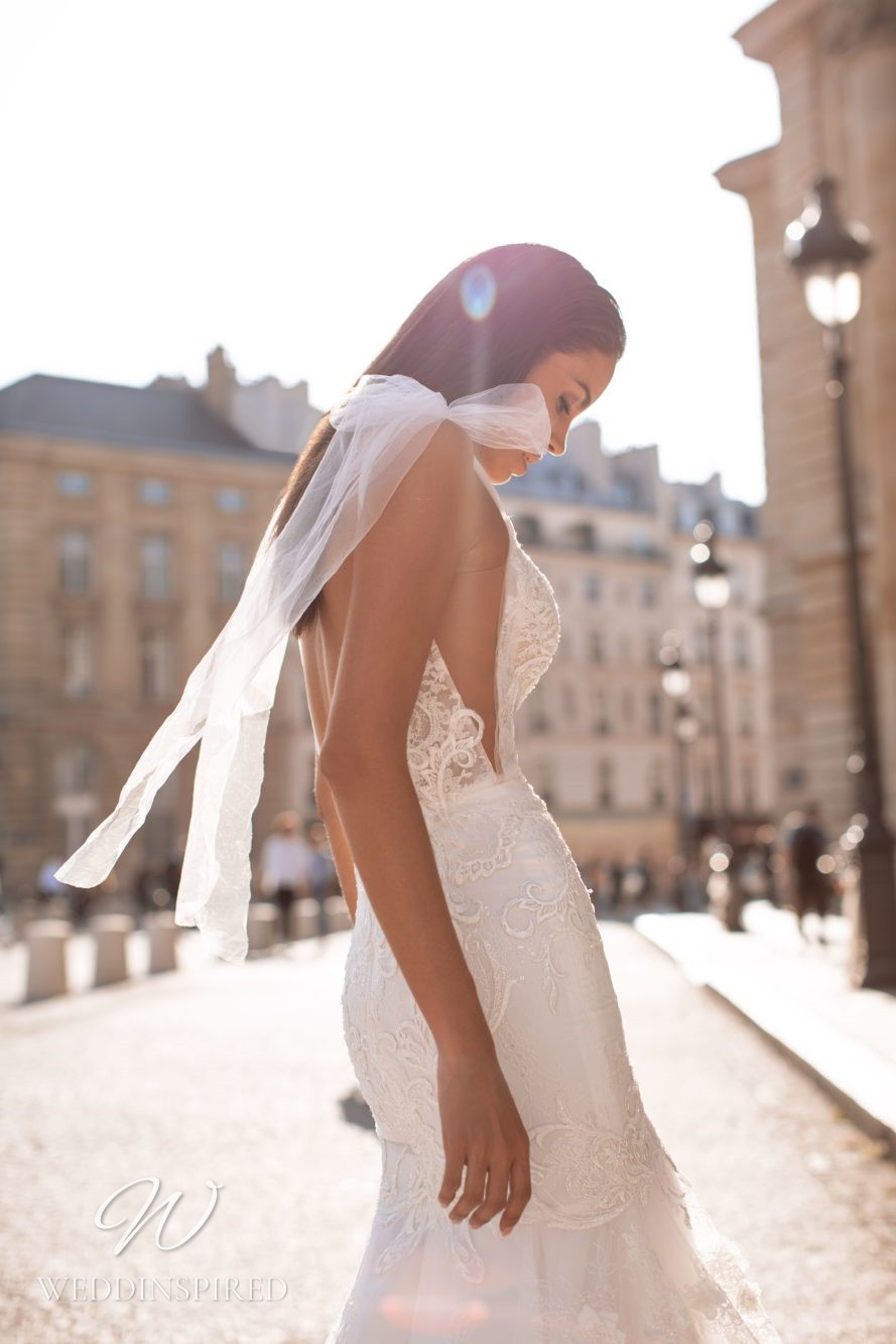 A Milla Nova lace mermaid wedding dress with a tulle bow