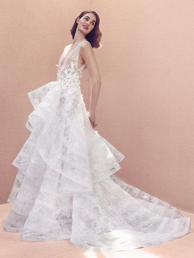 An Oscar de la Renta ball gown wedding dress with a layered tulle skirt, straps, a deep v neckline and flowers