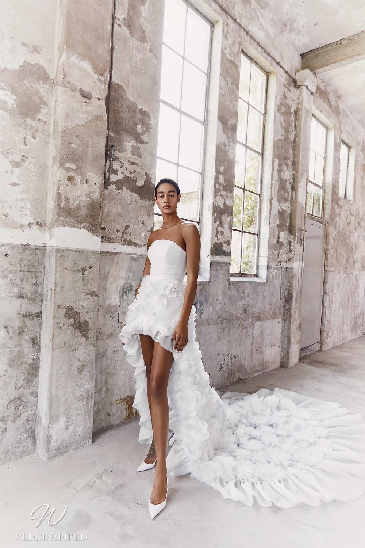 A Viktor & Rolf Fall/Winter 2021 short strapless wedding dress with a ruffle skirt and a train