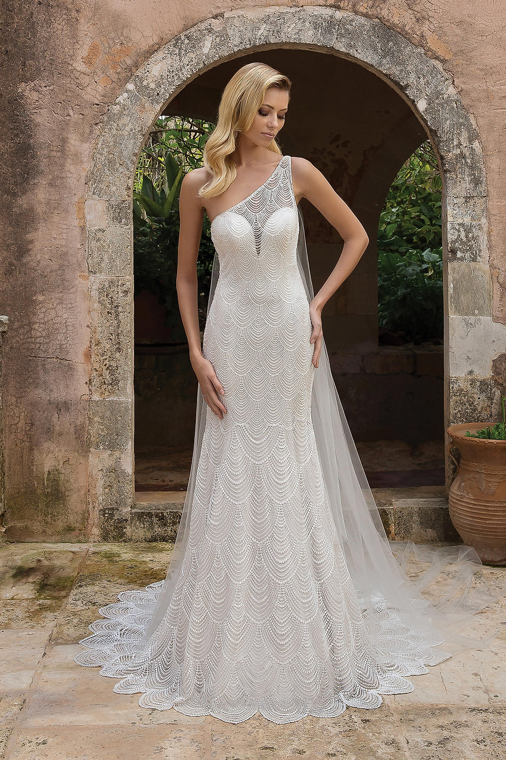 A one shoulder mermaid wedding dress with an overlay and a scallop pattern