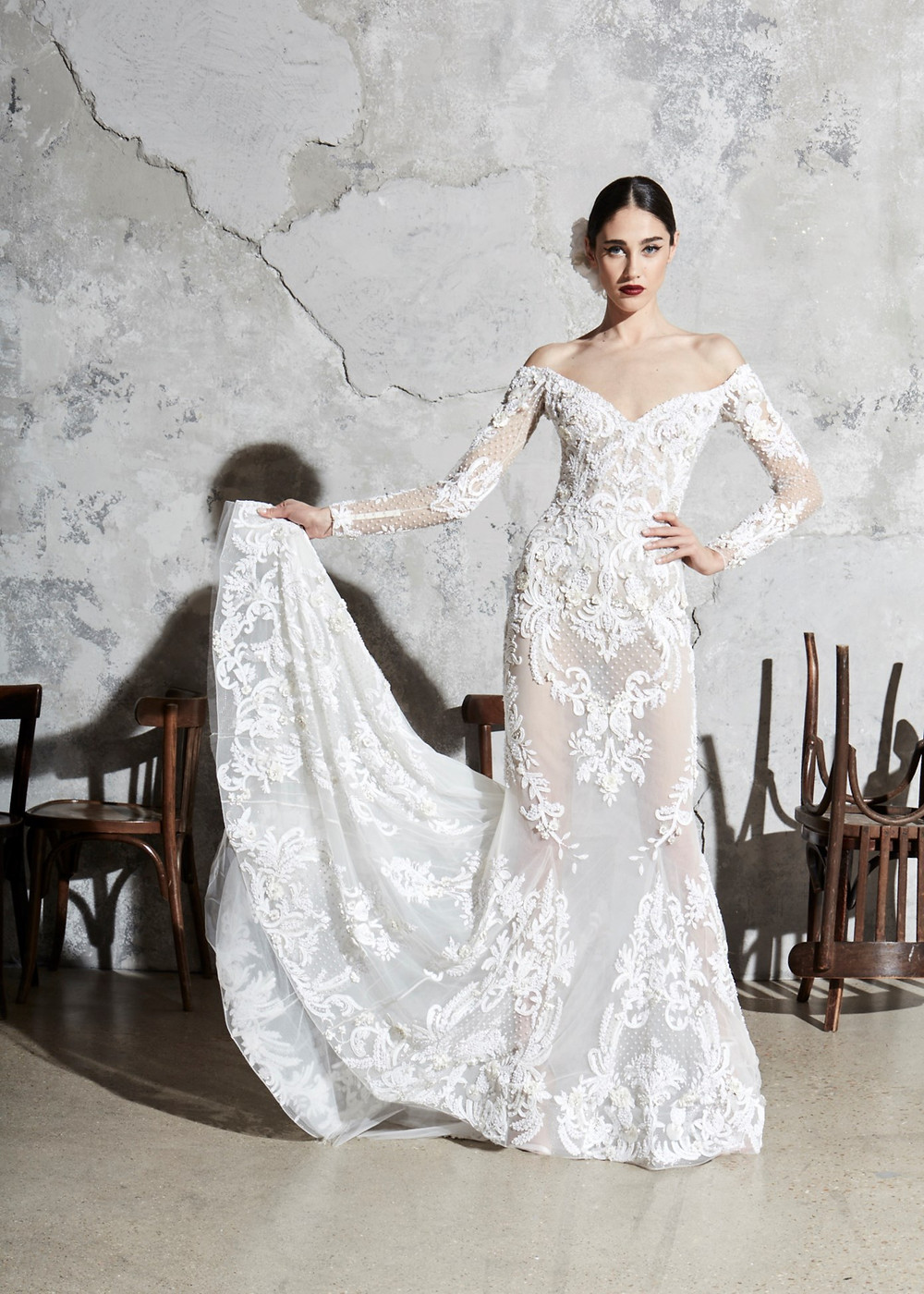 An off the shoulder, lace A-line wedding dress with long sleeves