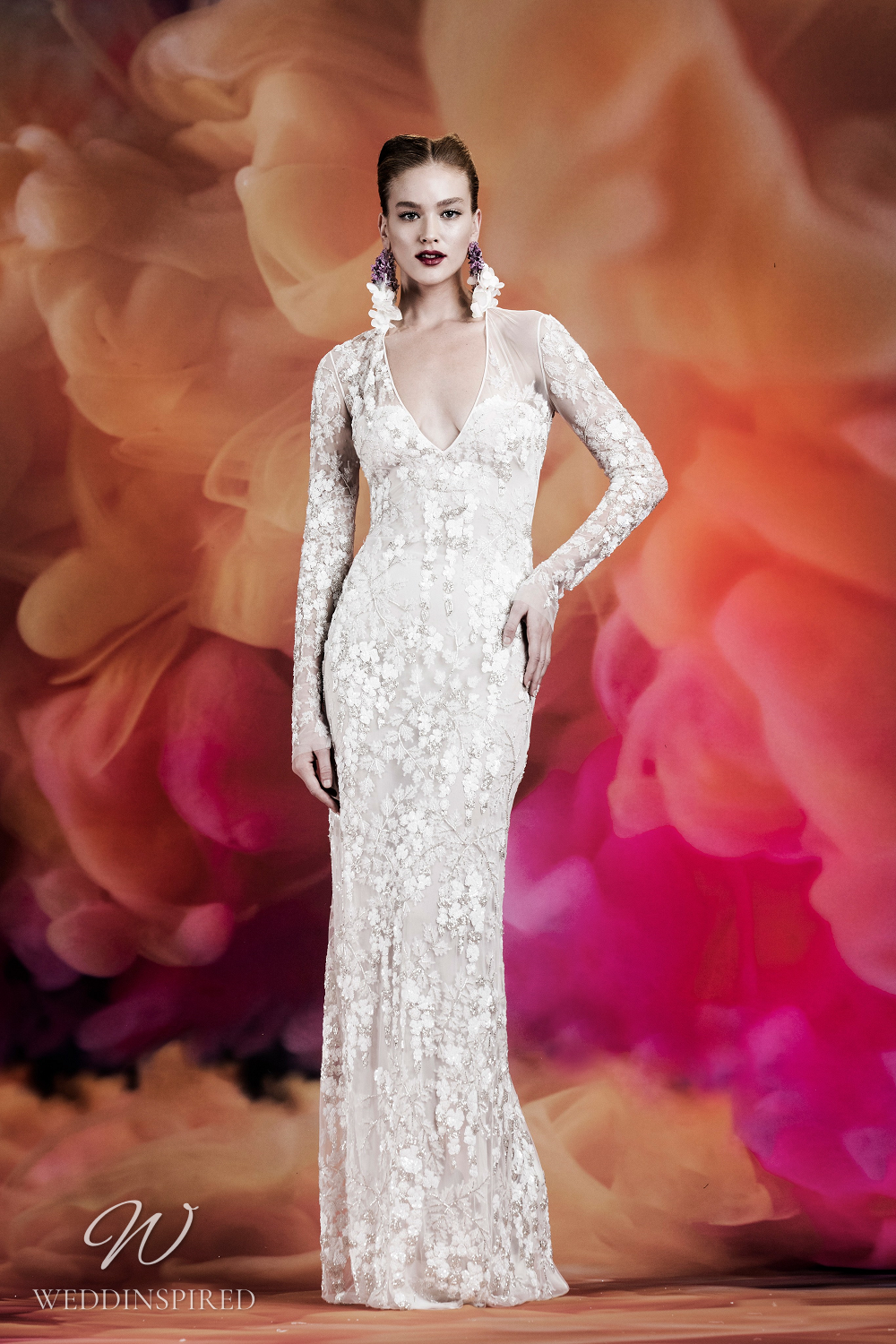 A Naeem Khan lace column wedding dress with illusion sleeves and a low v neckline