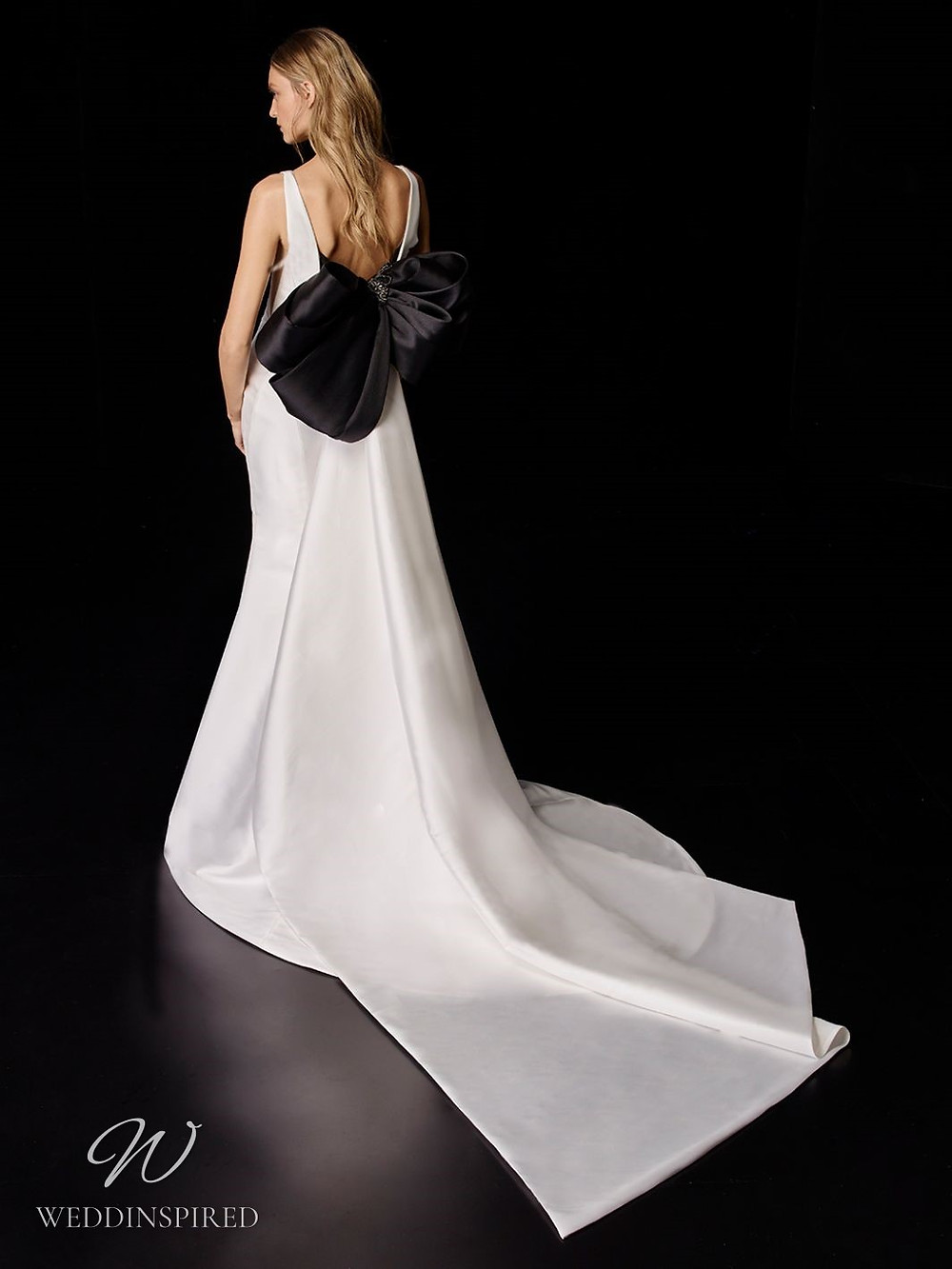 An Enzoani silk mermaid wedding dress with a low back and a big black bow