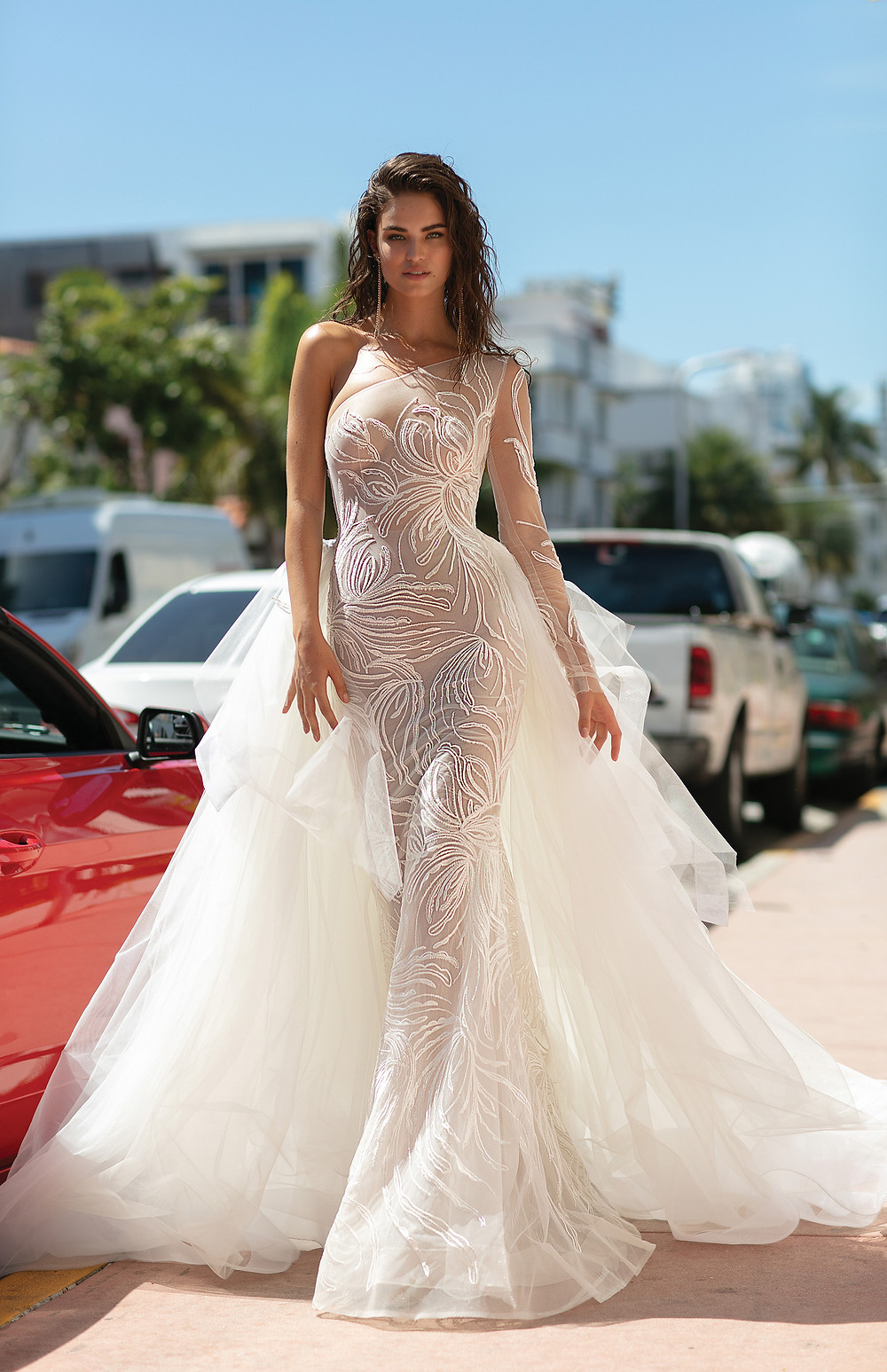 A sexy one shoulder mermaid wedding dress with a detachable skirt or overskirt and a swirl pattern