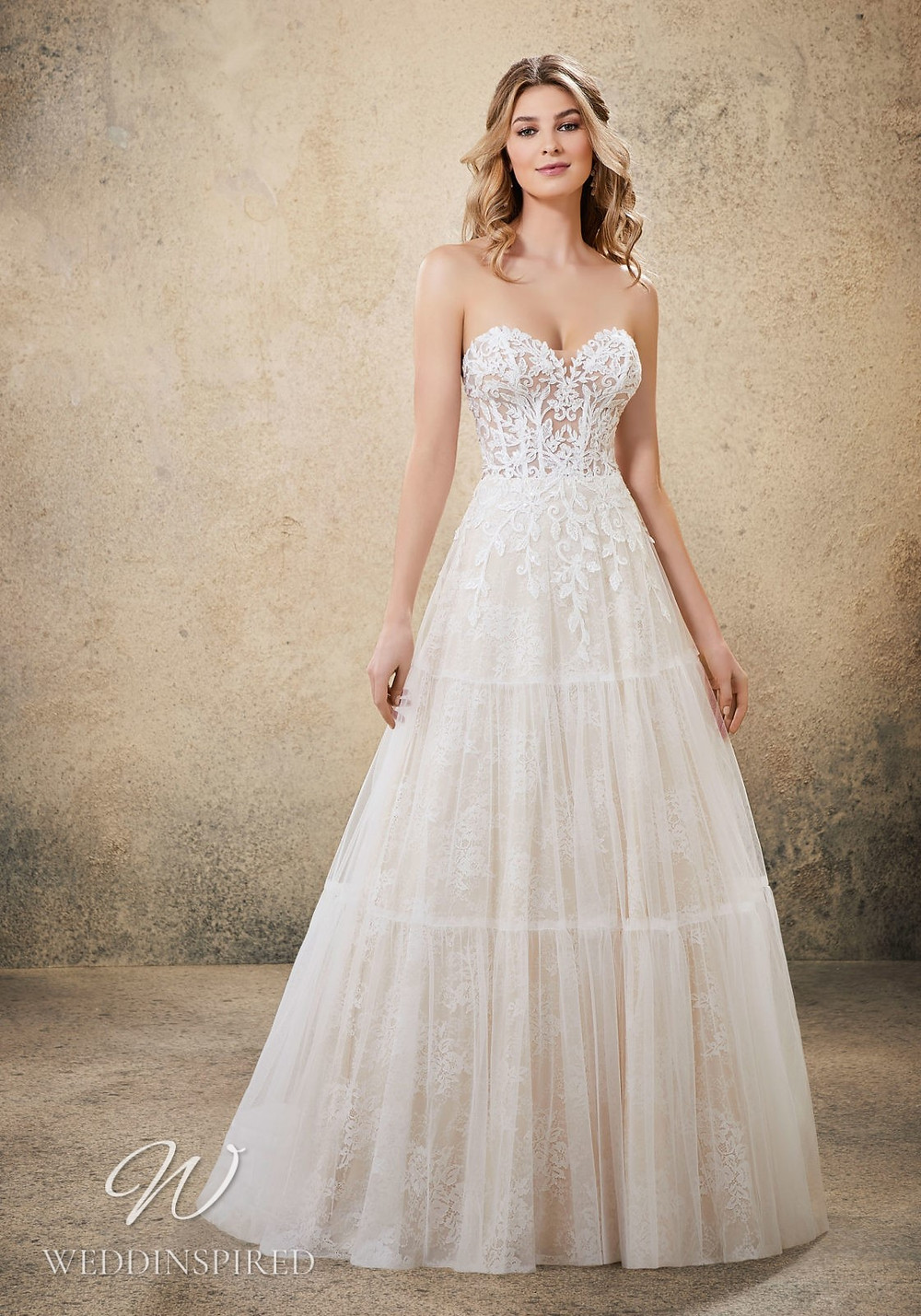 A Madeline Gardner blush strapless lace A-line wedding dress