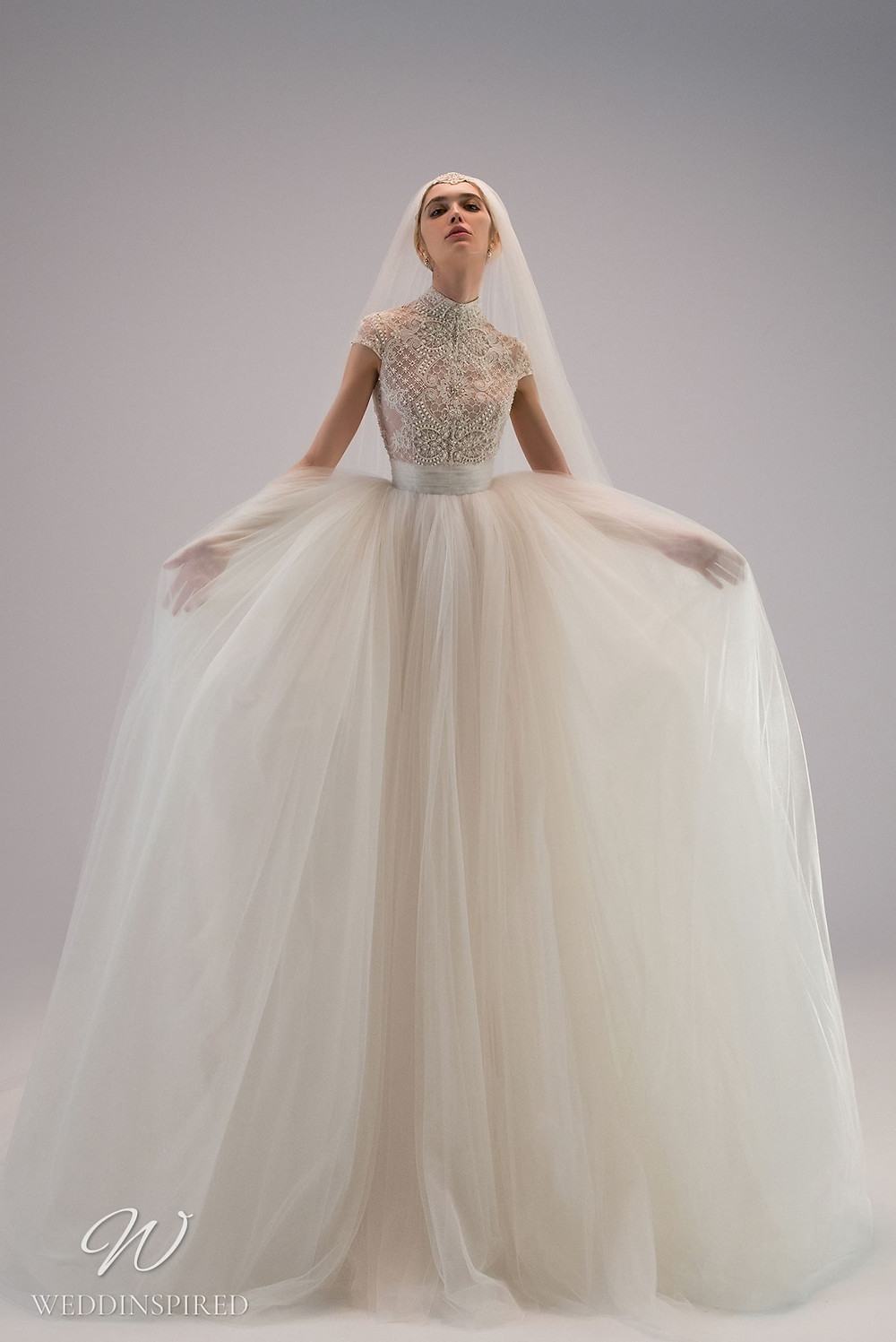 An Ersa Atelier 2021 modest ball gown wedding dress with a detachable chiffon skirt, a lace bodice, cap sleeves and beading