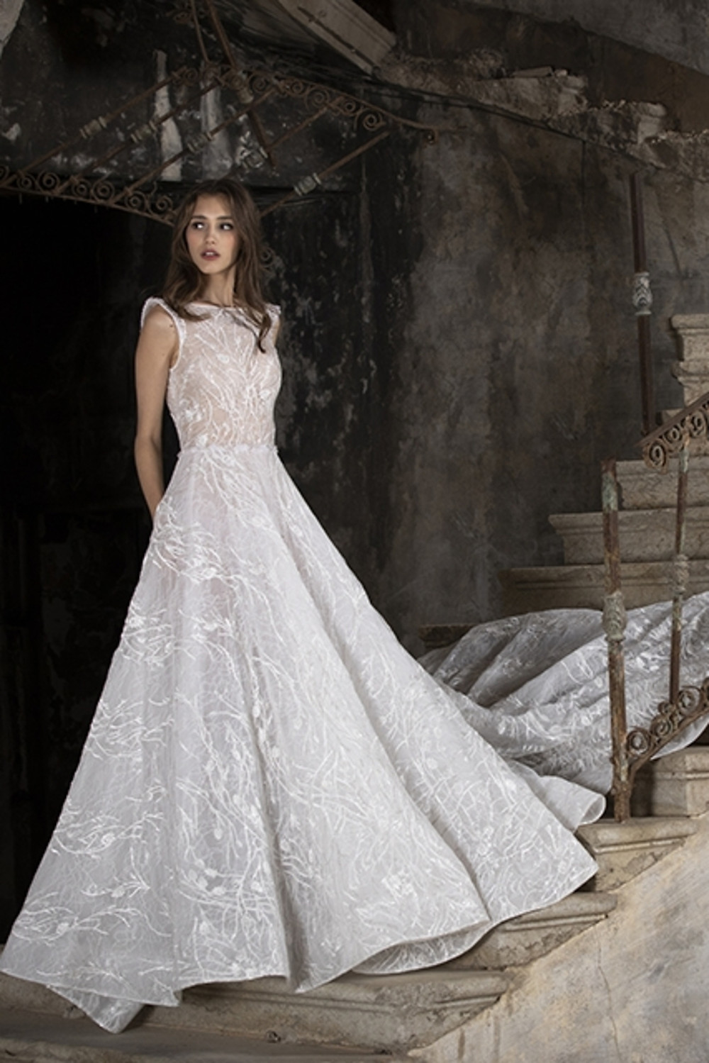 An A-line wedding gown with bold lace embroideries and boat neckline