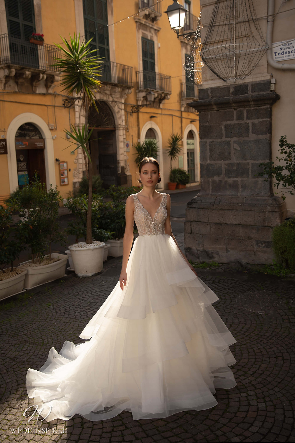 A Naviblue lace and tulle A-line wedding dress with straps and a layered skirt