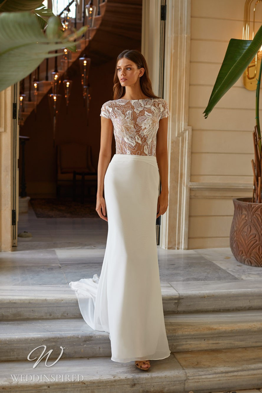 A Milla Nova 2021 lace and chiffon sheath wedding dress with cap sleeves and a high neckline