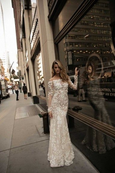 A lace, off the shoulder sheath wedding dress with long sleeves