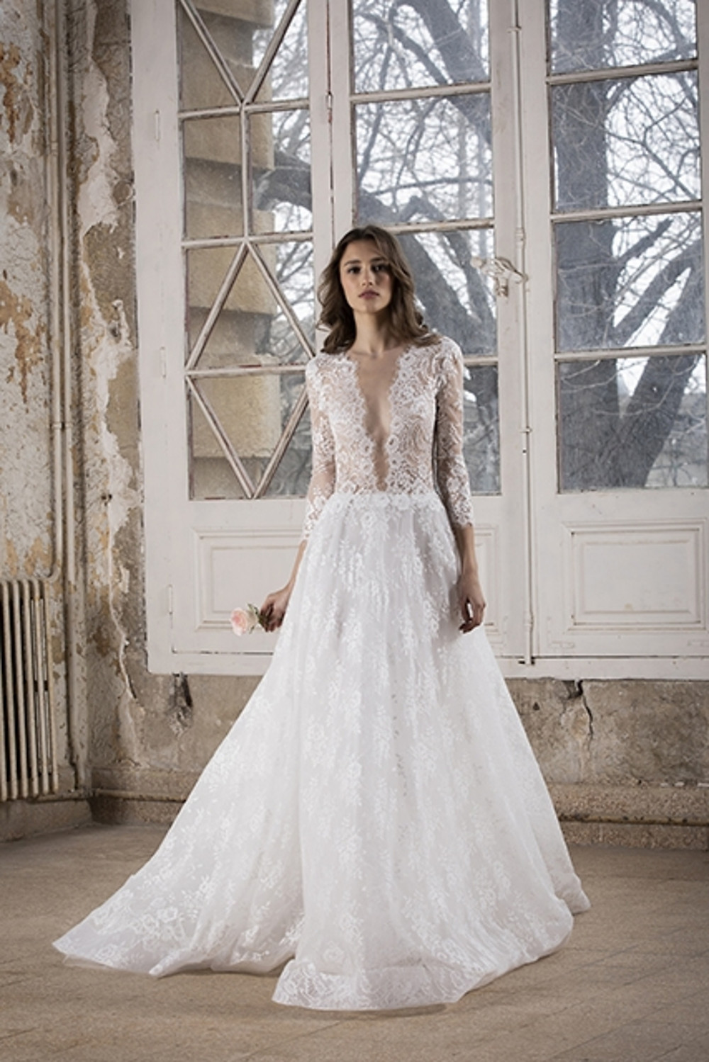 A deep-V wedding gown featuring a lace bodice with a plunging neckline, three quarter sleeves, and an embroidered tulle skirt