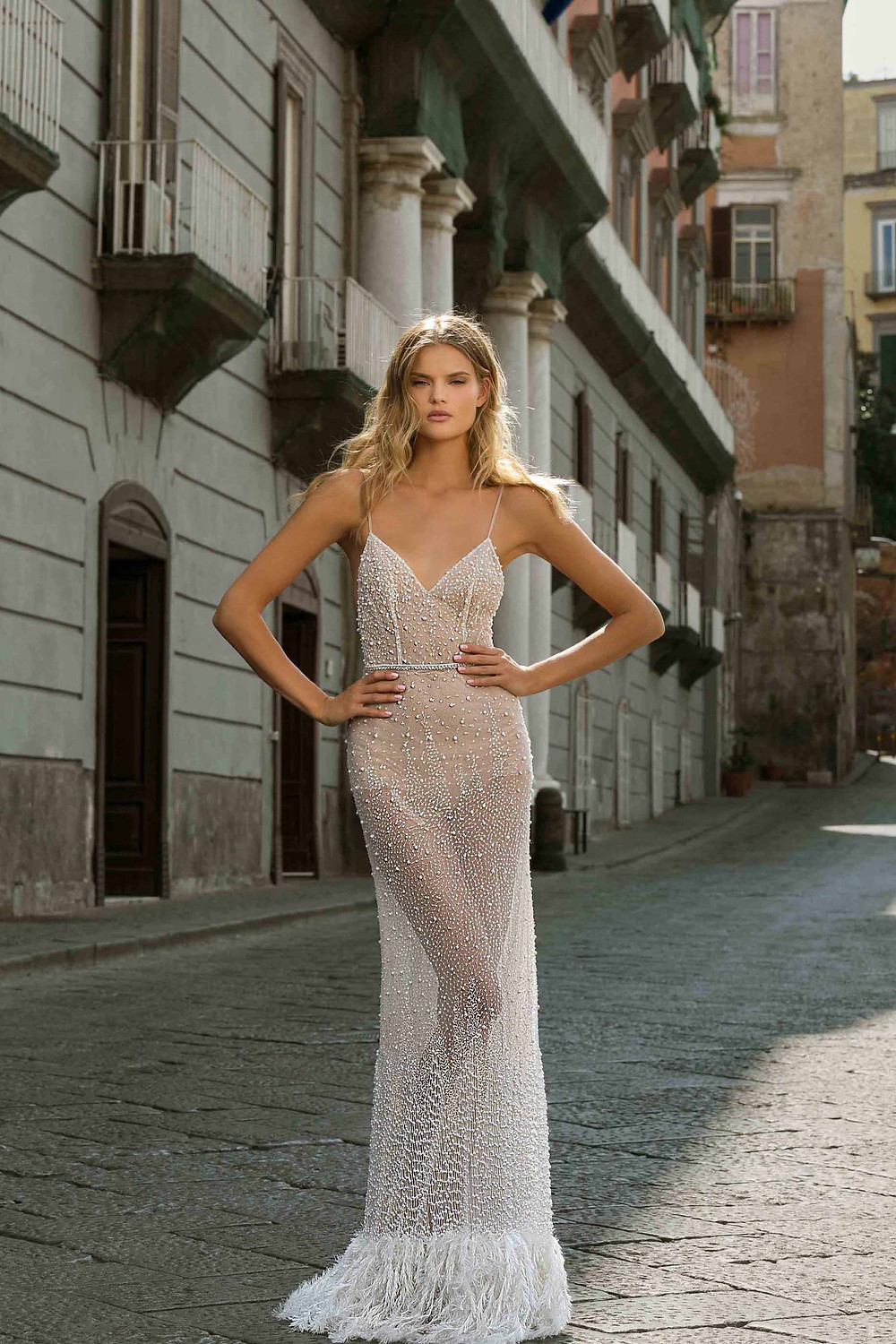 A sparkly sheath wedding dress, with thin straps, feathers and crystals