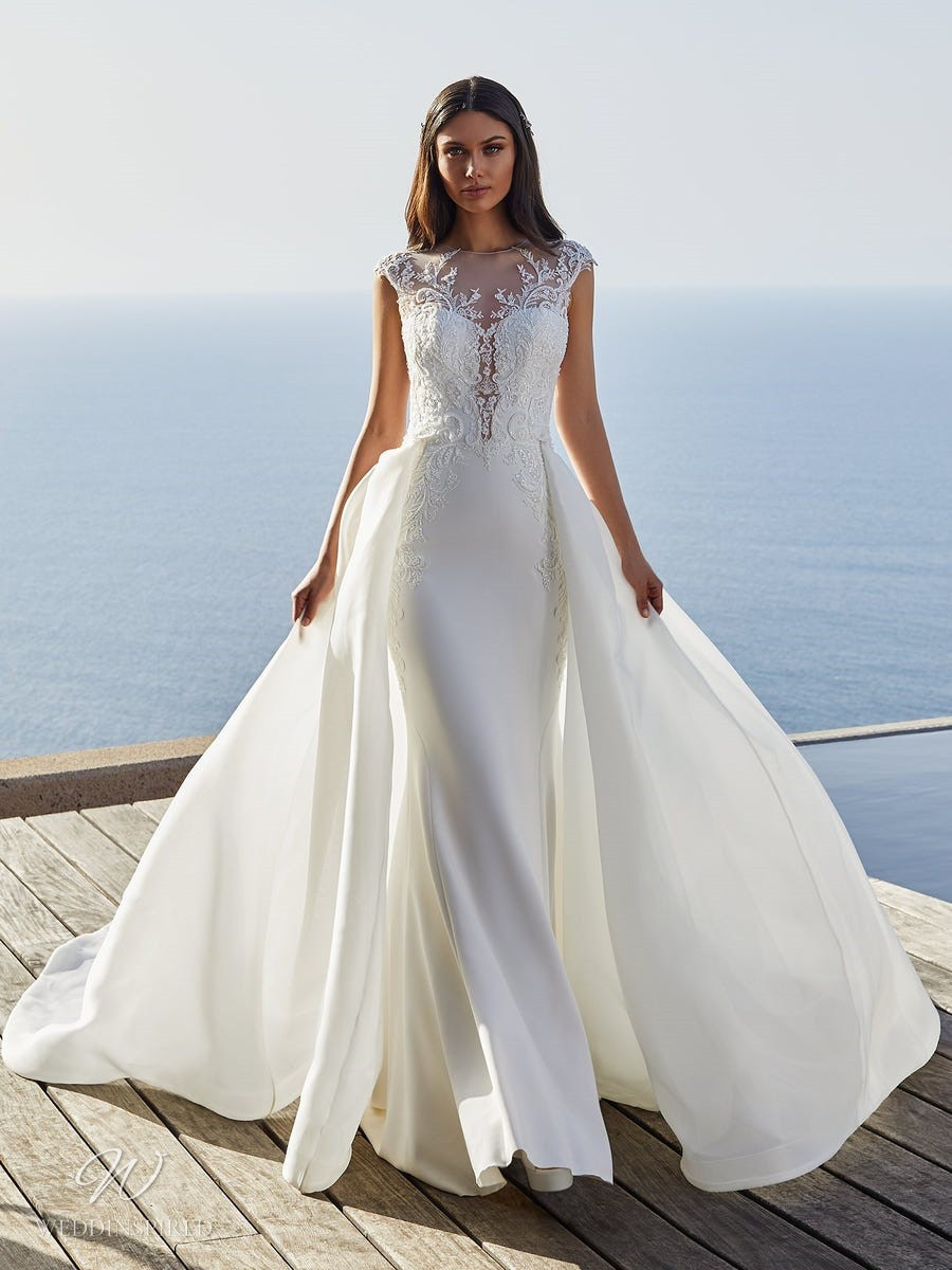 A Pronovias 2021 lace and crepe mermaid wedding dress with a detachable skirt and an illusion neckline