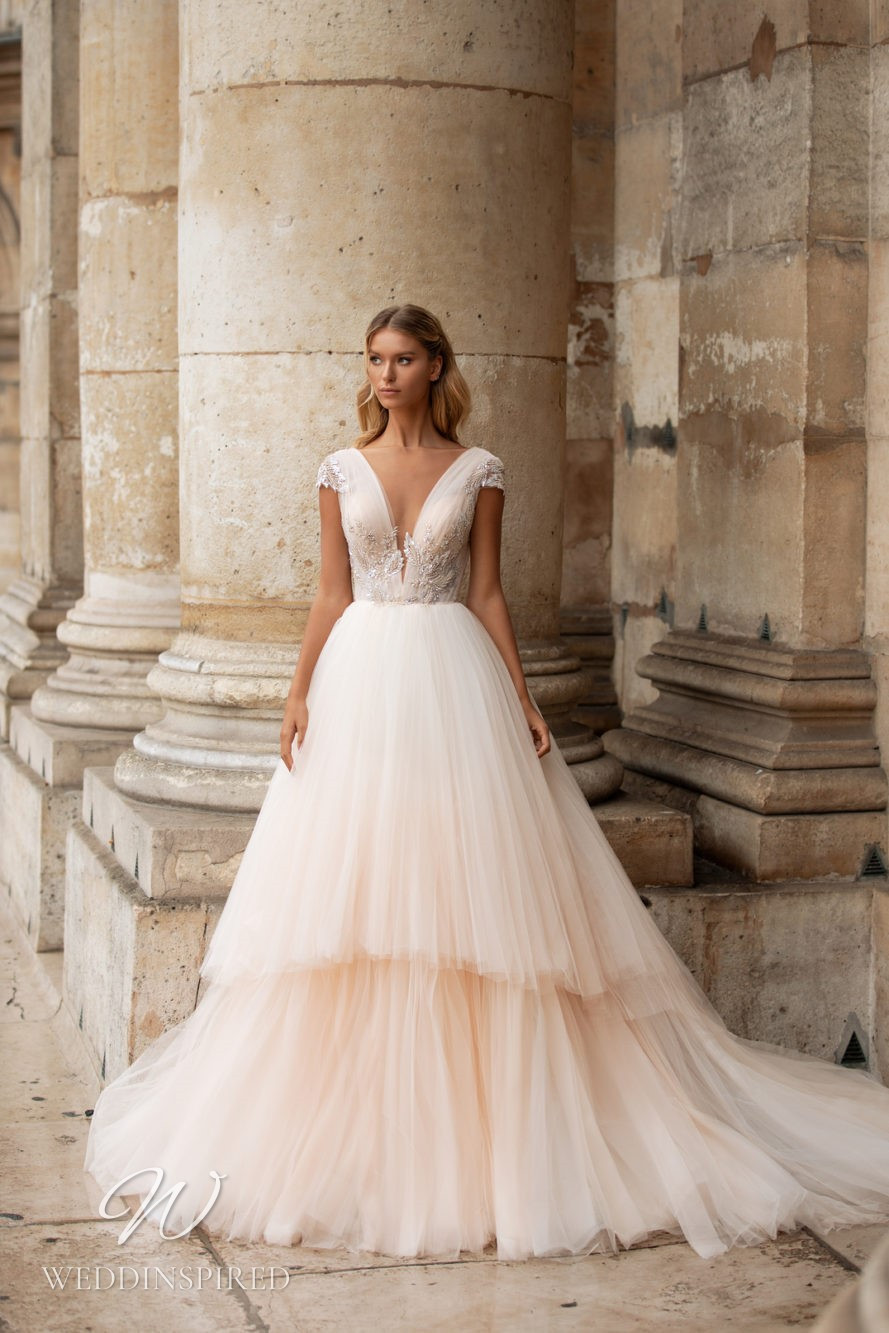 A Milla Nova blush tulle ball gown wedding dress with cap sleeves