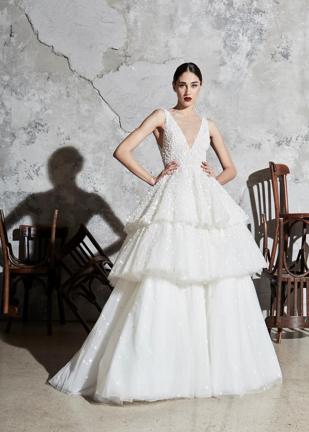 A Zuhair Murad ball gown wedding dress with a layered skirt, a deep v neckline and pearls