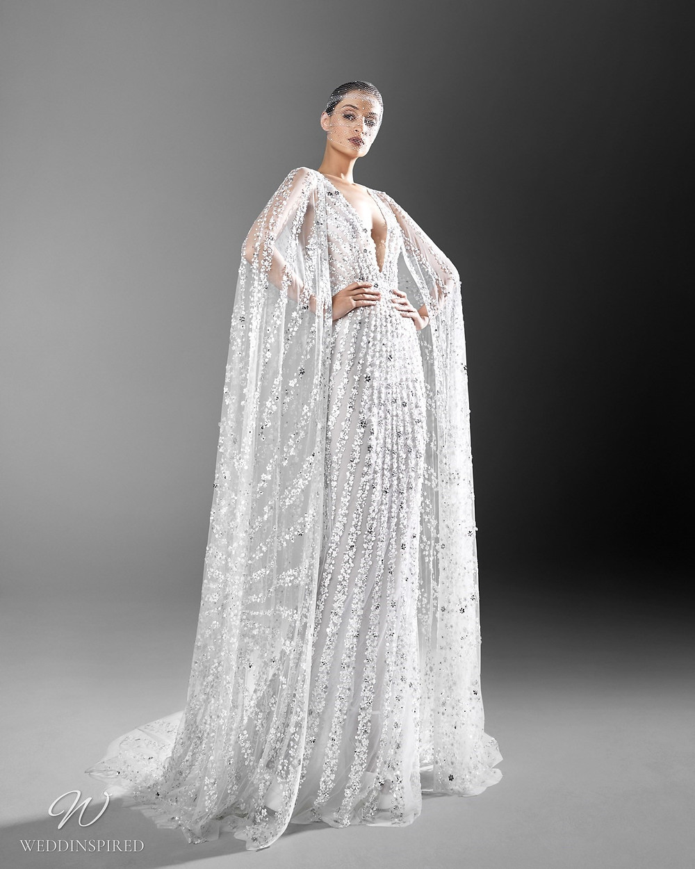 A Zuhair Murad crystal embellished mermaid wedding dress with low v neckline and an illusion cape