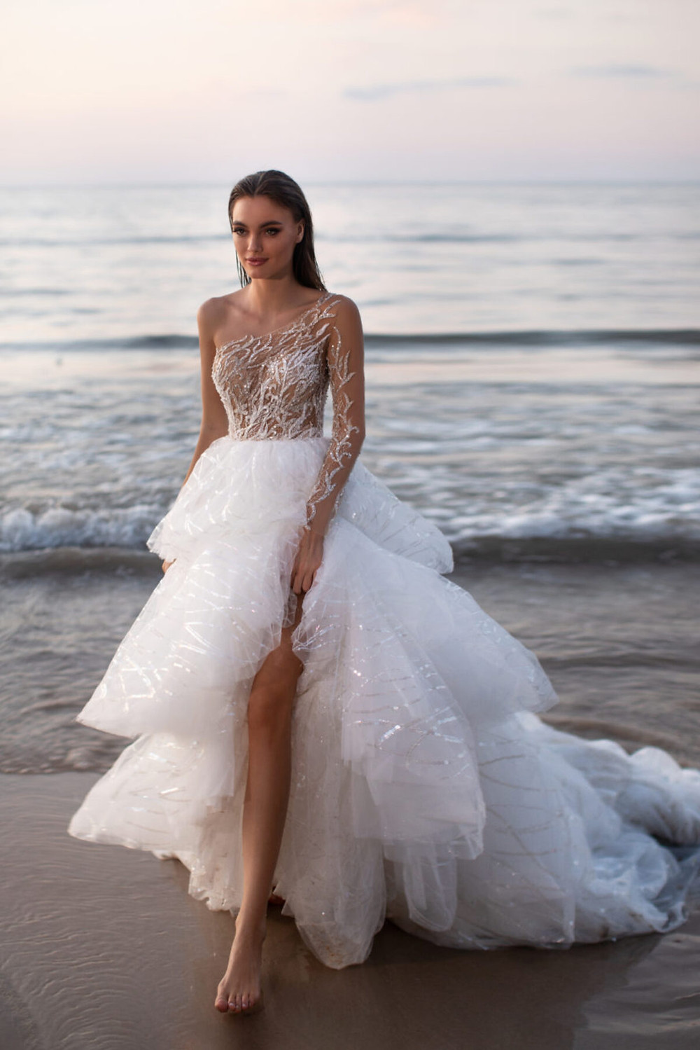 A one shoulder, ball gown wedding dress with a tiered skirt and sparkles
